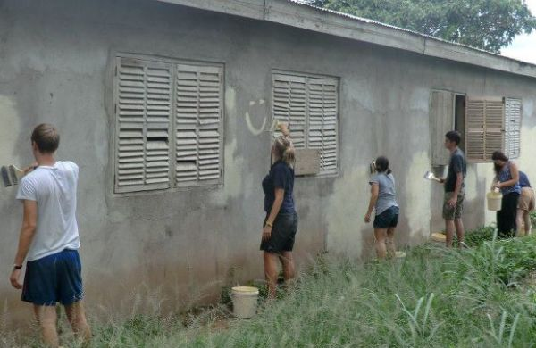 A photo of some British volunteers painting the side of a school building in Ghana