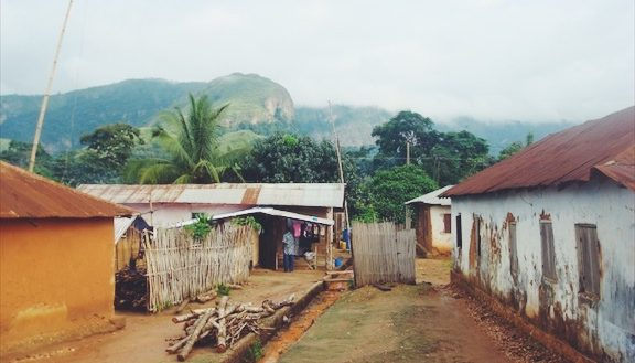 A view of a Ghanaian village with lush green mountains in the background