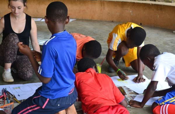 A British volunteer draws and paints with a group of Ghanaian children